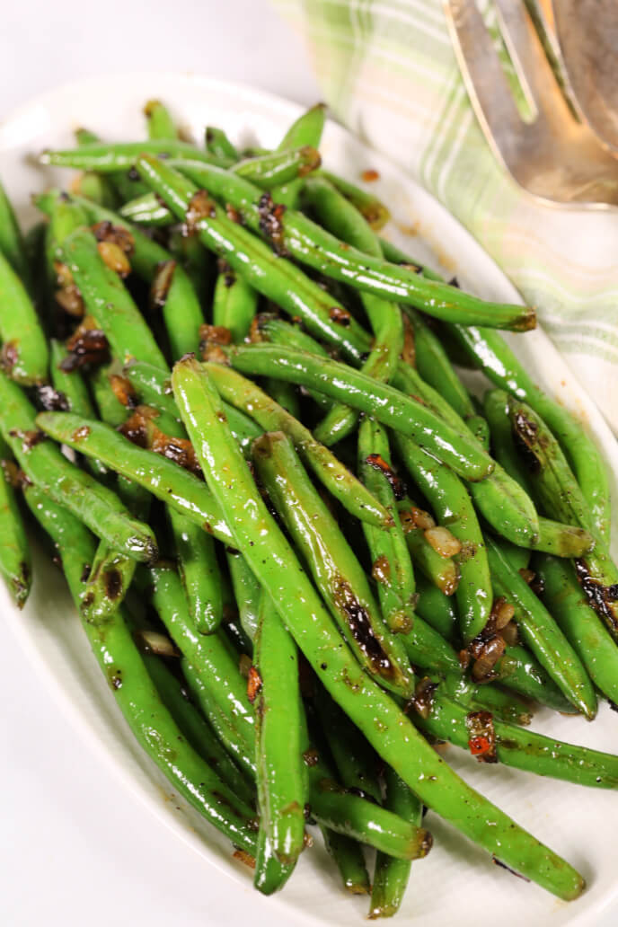 Sweet and spicy green beans on a white plate with a green plaid napkin