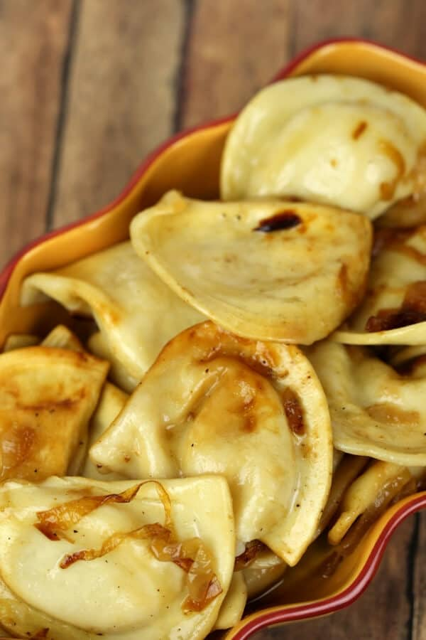 Crock pot pierogie in a yellow dish on wooden table