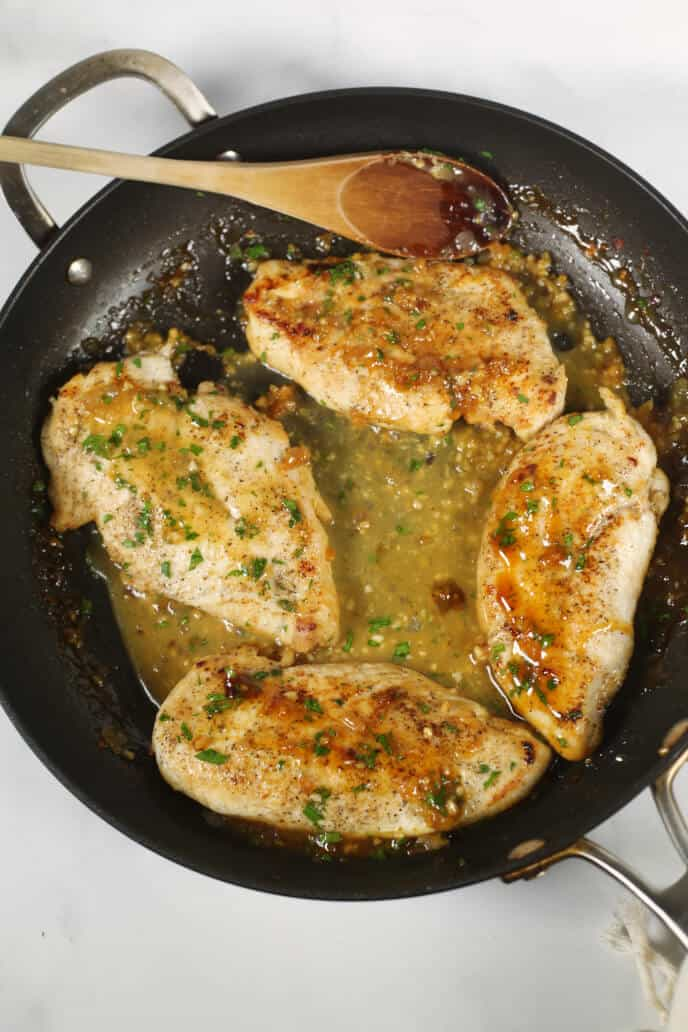 ginger chicken in a skillet with a wooden spoon