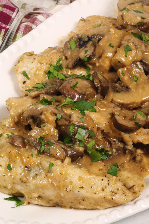 Instant Pot Chicken Marsala on a white platter with a plaid napkin