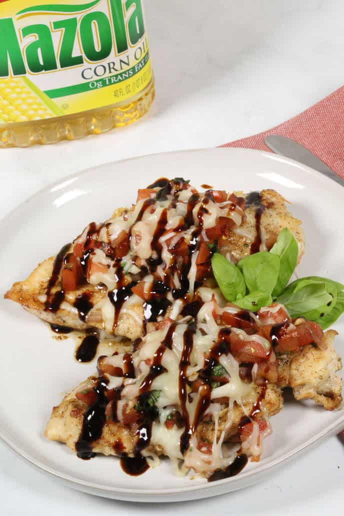 Bruschetta chicken on a white plate with a red napkin and mazola corn oil