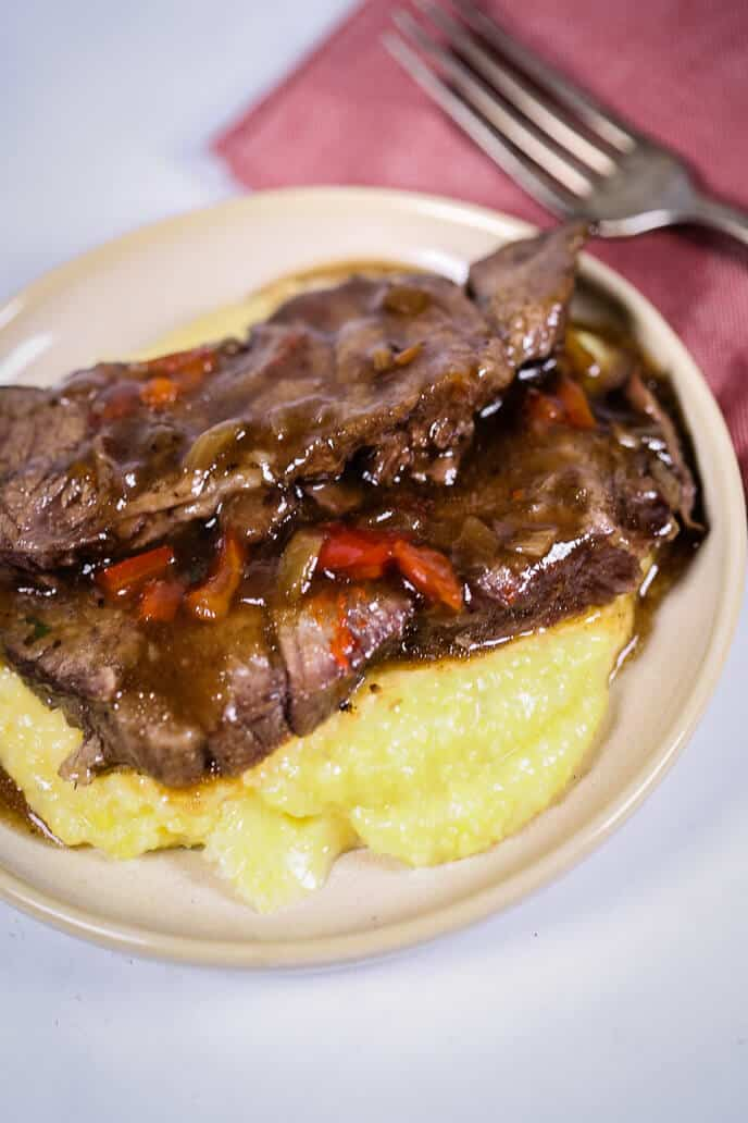 Creamy polenta on a plate with Italian beef on top of it