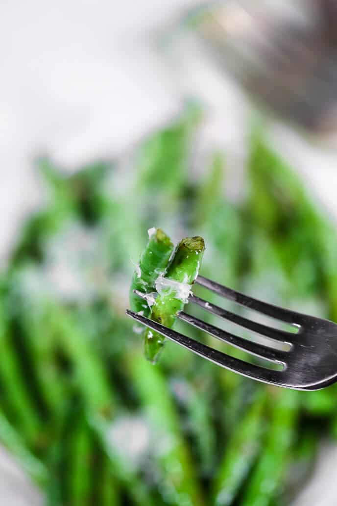 Parmesan green beans on a fork with more beans in the backgroun