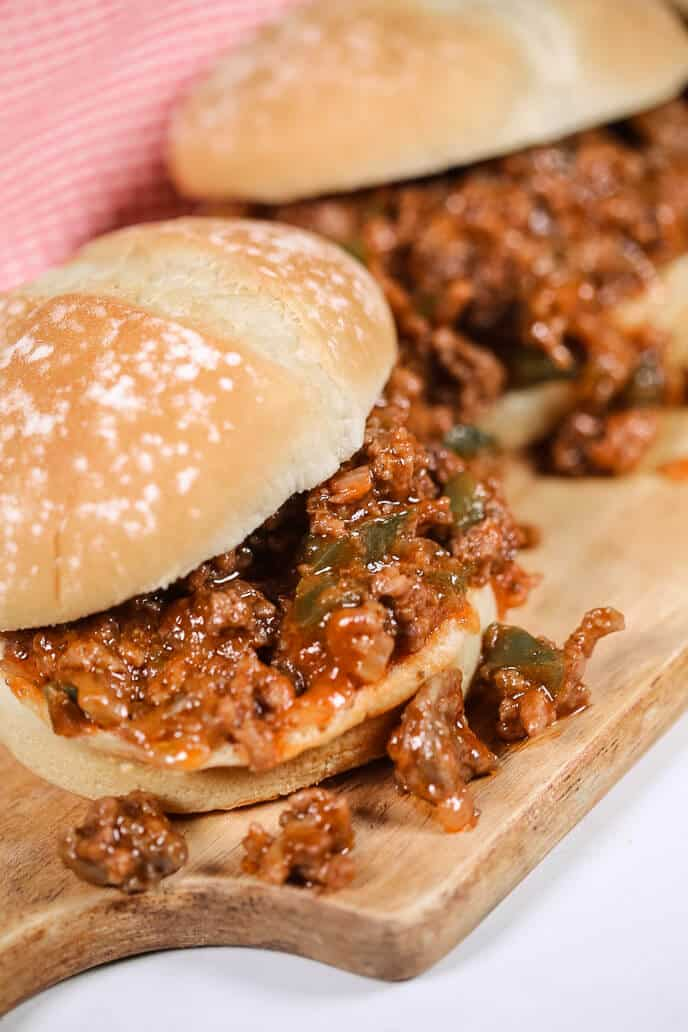 sloppy joes recipe on a wooden plank with a checkered napkin
