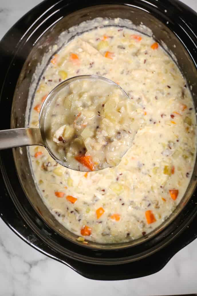Slow Cooker Chicken and wild rice soup in a ladle