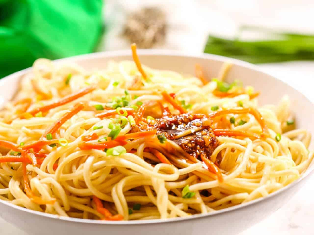 Easy sesame noodles in a white bowl with a green napkin