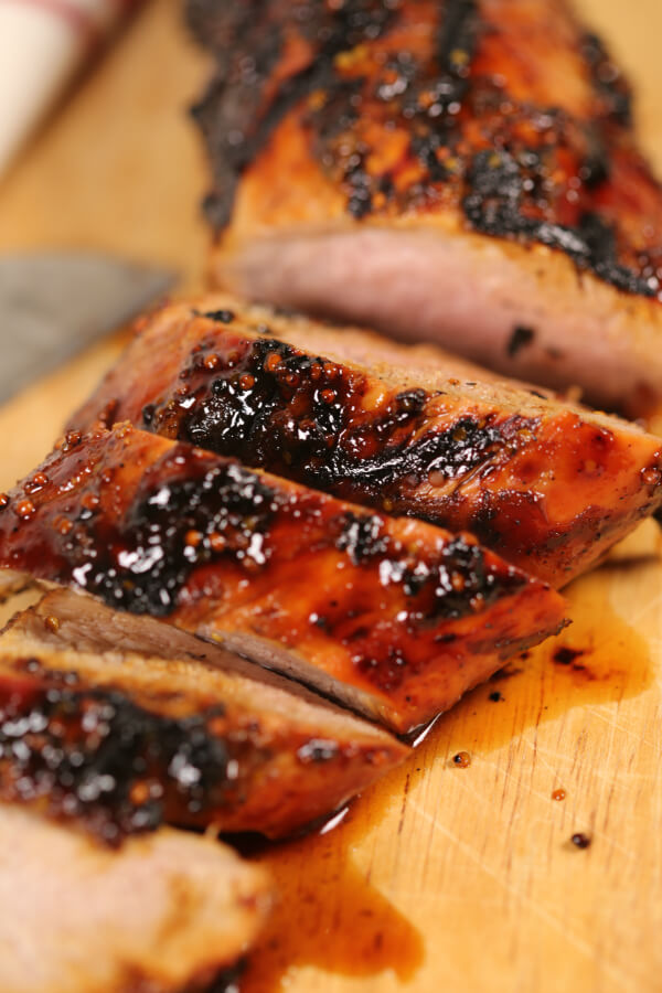 grilled pork tenderloin sliced on wooden cutting board