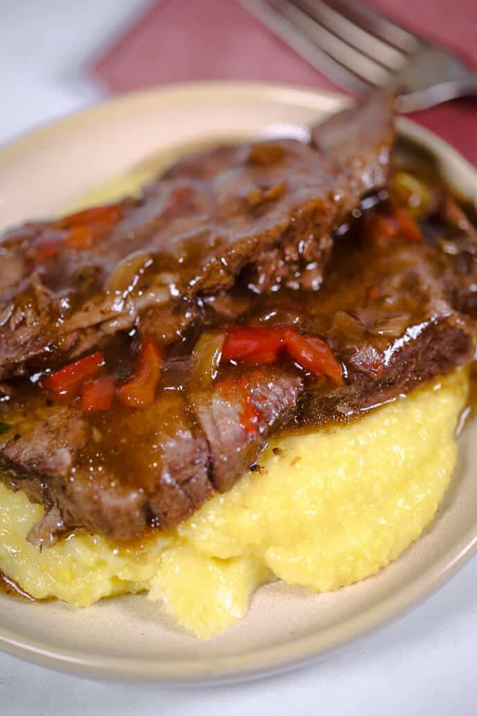Slow cooker italian beef served over polenta with a napkin and fork