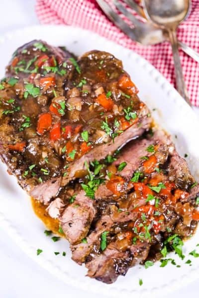 Slow cooker italian beef on a white plate with a checked napkin and silverware
