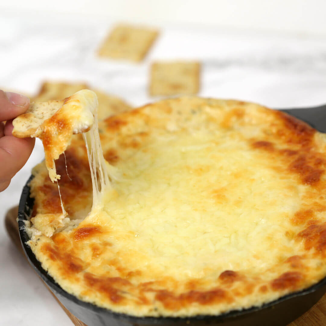 Dipping a cracker into white pizza dip in a skillet