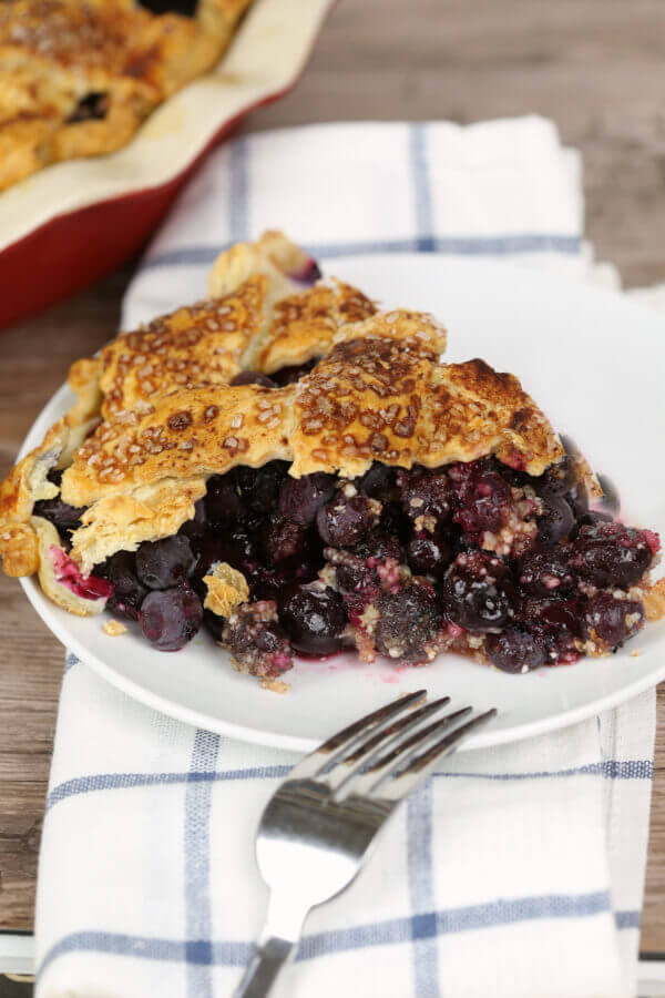 blueberry pie on a white plate with a white checkered napkin with a silver fork.