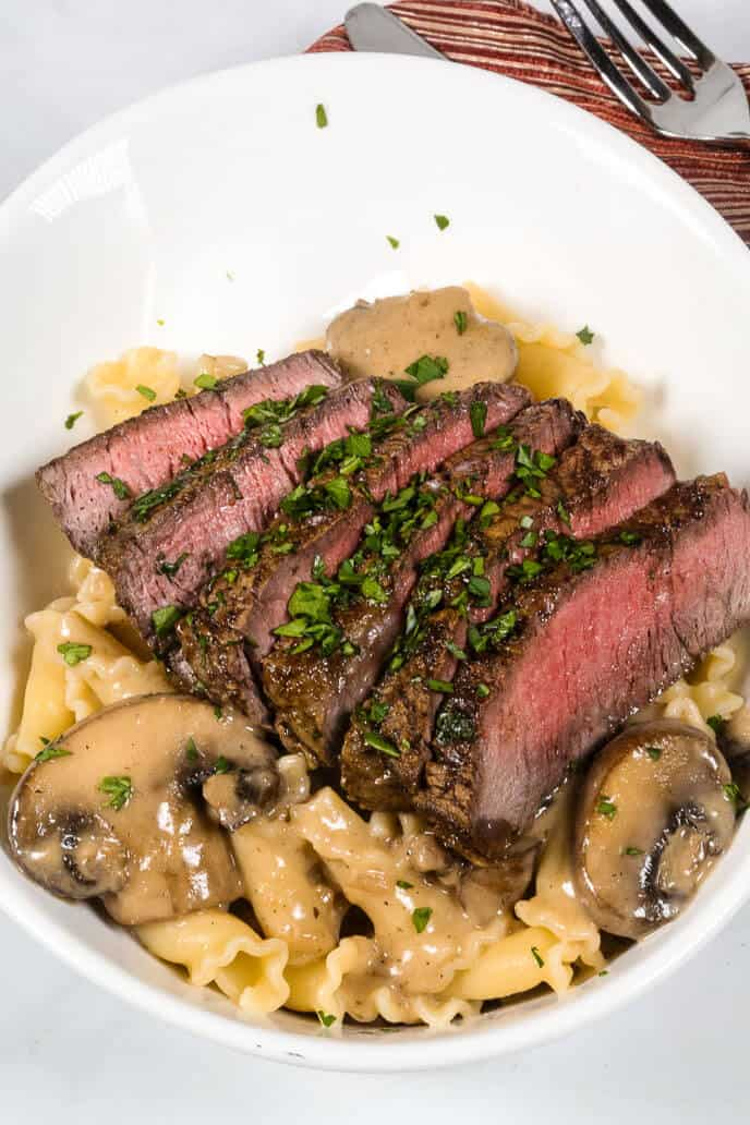 Filet Mignon in Sherry Mushroom Cream Sauce in a white bowl with a fork