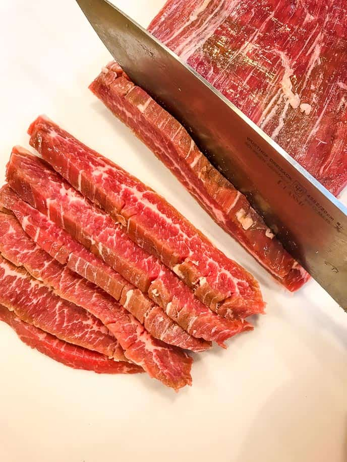 picture of how to cut flank steak with a metal knife