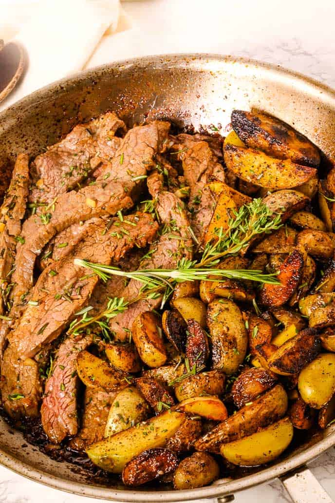 skillet with steak potatoes and herbs