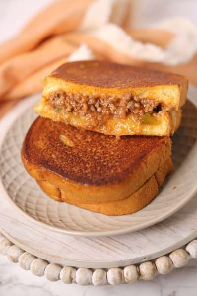 Sloppy joe grilled cheese on a white place with peach napkin