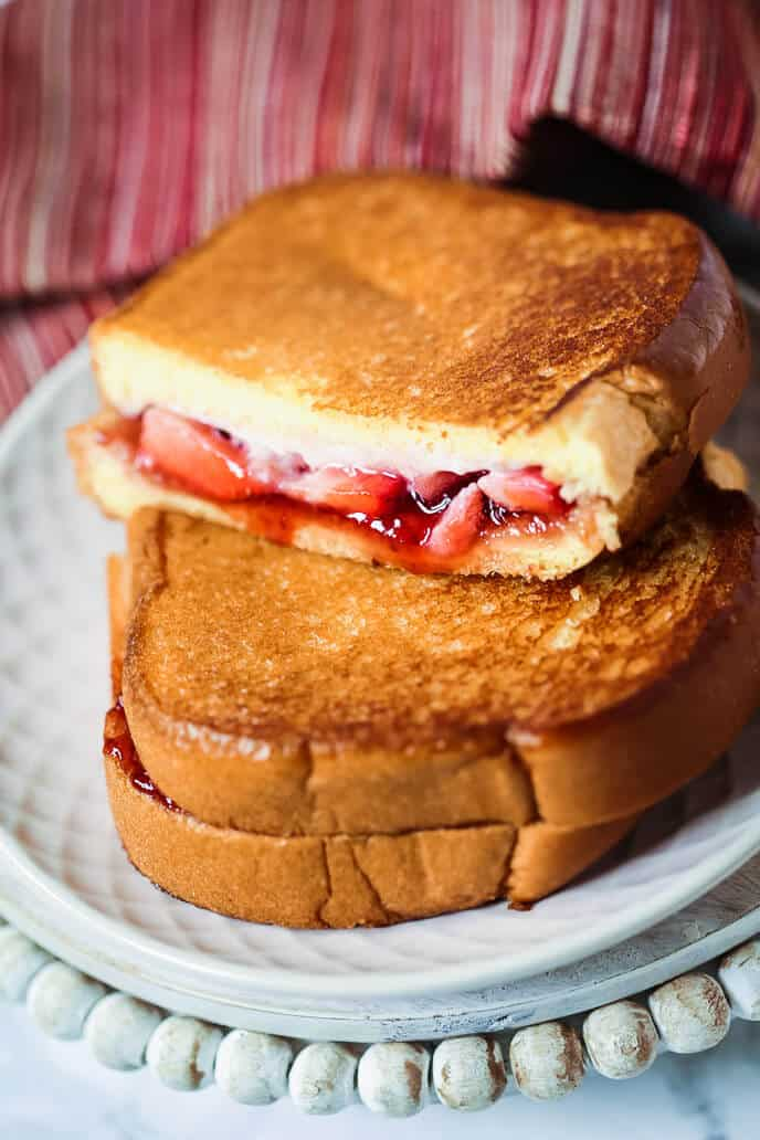 strawberry grilled cheese on white plate with red striped napkin