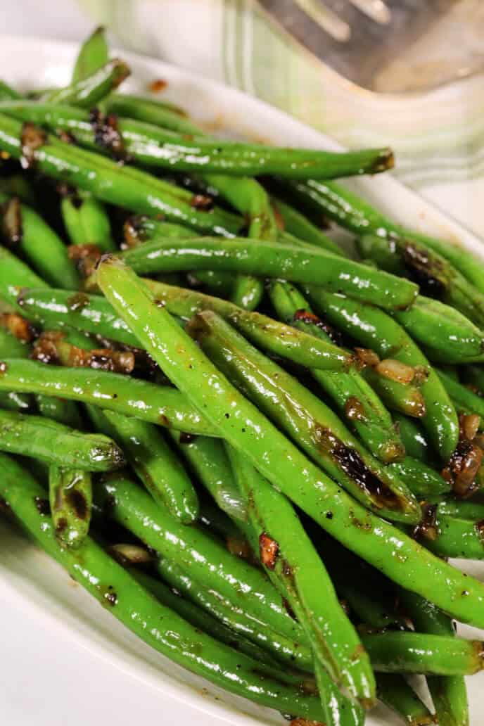 Sweet and spicy green beans on a white dish with a green plaid napkin