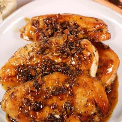 Honey glazed chicken on a white plate with orange napkin and silverware