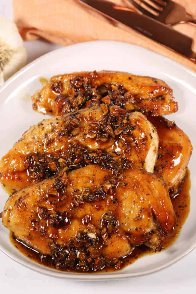 Honey glazed chicken on a white plate with orange napkin and silverware