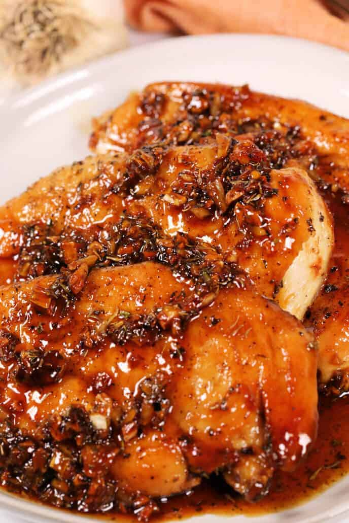 Honey glazed chicken on a white platter with garlic garnish