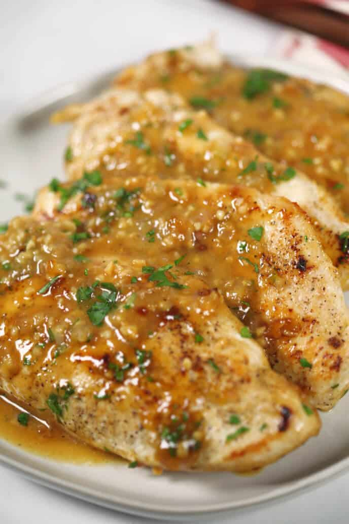 Ginger Chicken on a white plate with a striped napkin