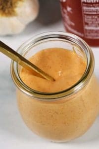 Boom Boom sauce in a glass jar with a spoon
