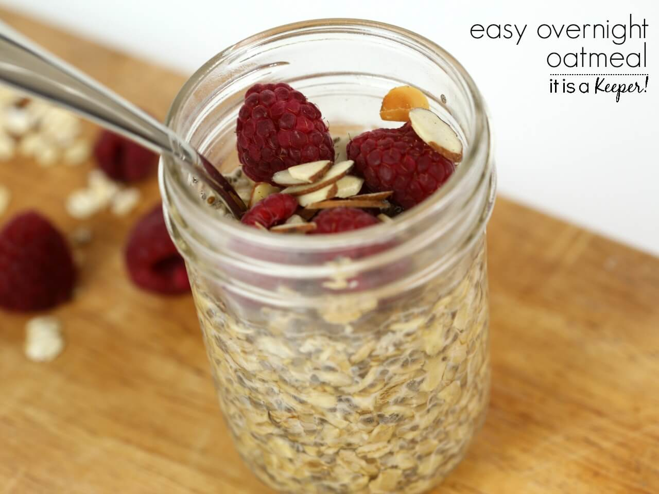 oatmeal topped with raspberries and almonds inside of a mason jar
