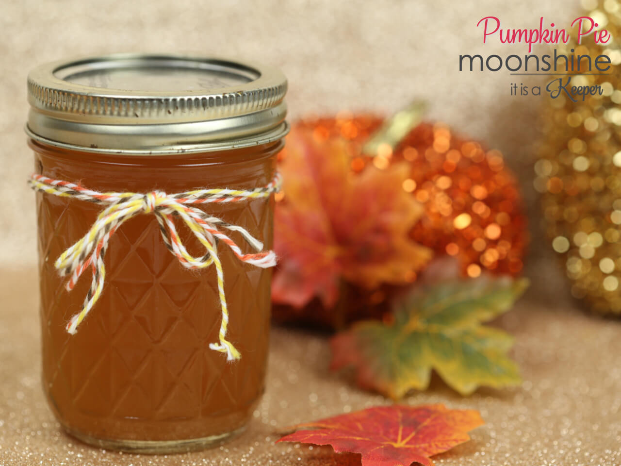 Pumpkin Pie Moonshine in a mason jar with leaves in the background.