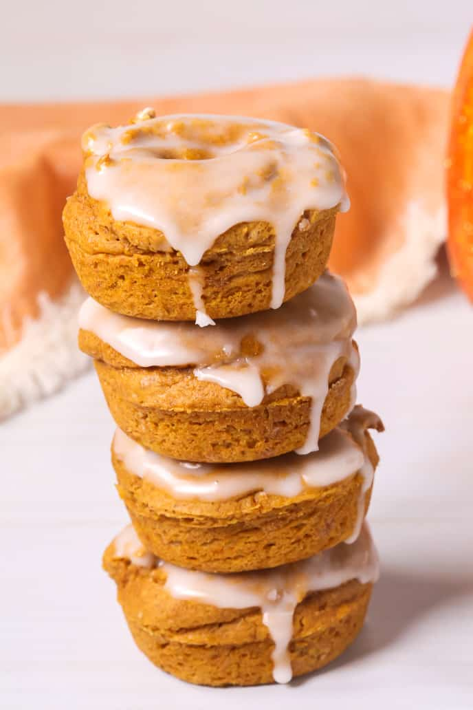 pumpkin donuts stacked on top of one another with an orange napkin in the background