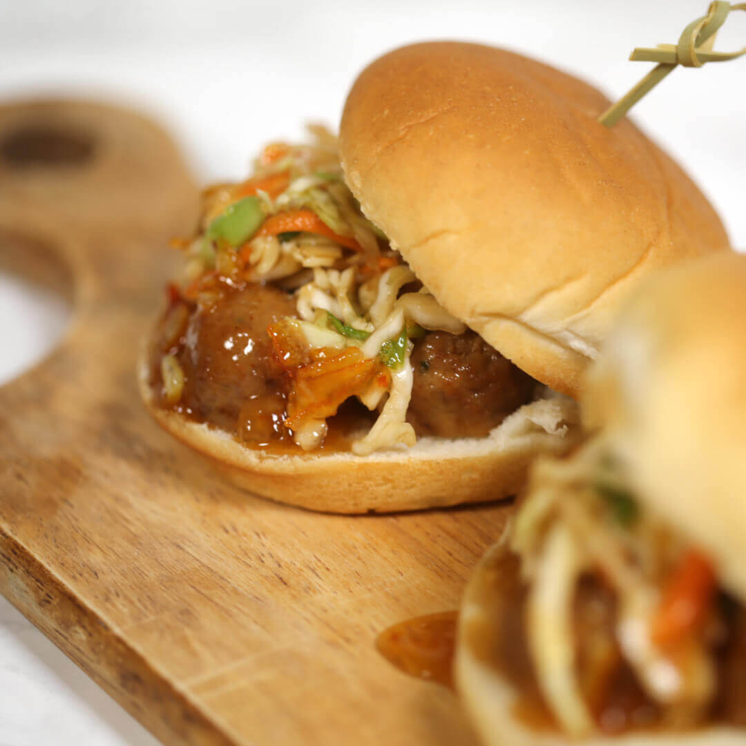 Korean Meatball Sliders on wooden plate.