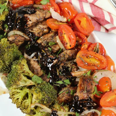 Balsamic Chicken Sheet Pan Recipe on a white platter with a pink and white napkin and fork