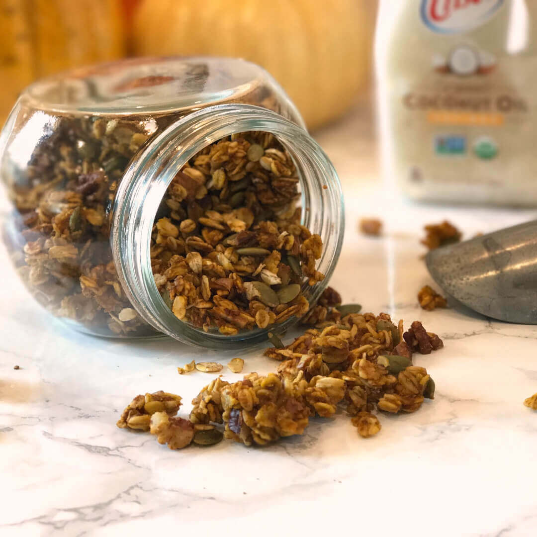 Pumpkin Spice Granola in a clear bowl with Crisco coconut oil in the background.