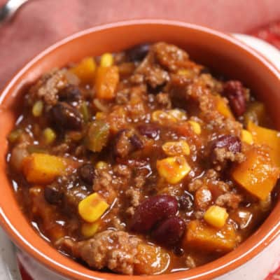 chili in a white crock on a red plate