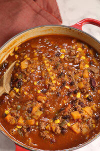 Chili in a large pot with a wooden spoon