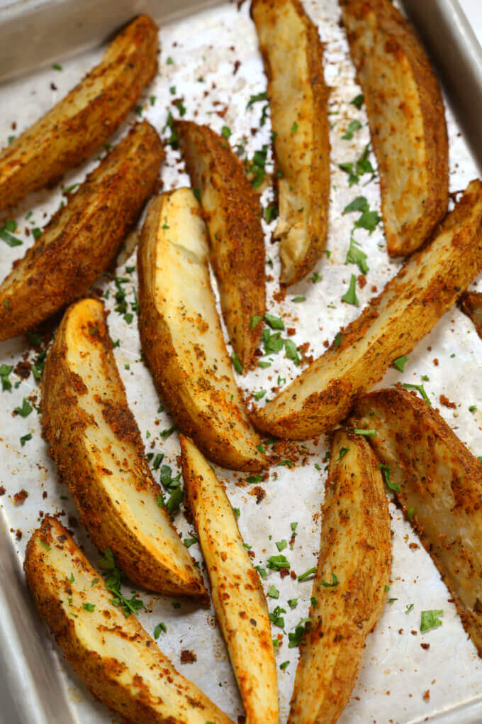 This Crispy Potato Wedges recipe is the perfect parter for burgers. They are made in the oven and oozing with flavor.