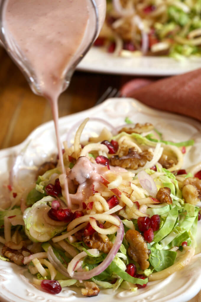 Harvest salad with layers of shaved brussels sprouts, apples, pomegranates, candied walnuts and a pomegranate vinaigrette on a white plate