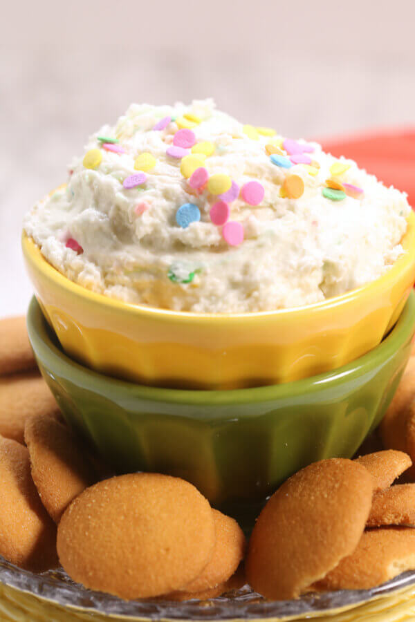 Confetti cake Batter Dip in a yellow and green bowl, with cookies around it.