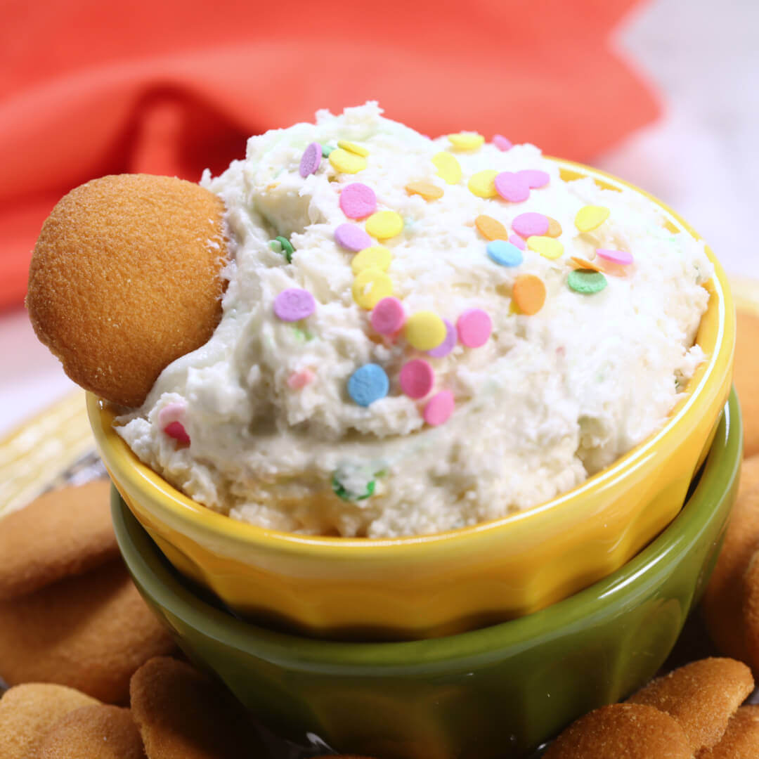 Cake mix Dip with a cookie in it, in a yellow and green bowl.