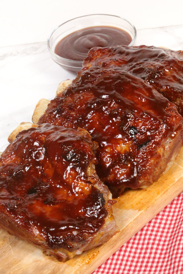 Instant Pot BBQ Ribs, on a wooden square plate with a checkered red napkin. BBQ Sauce in a small glass bowl.
