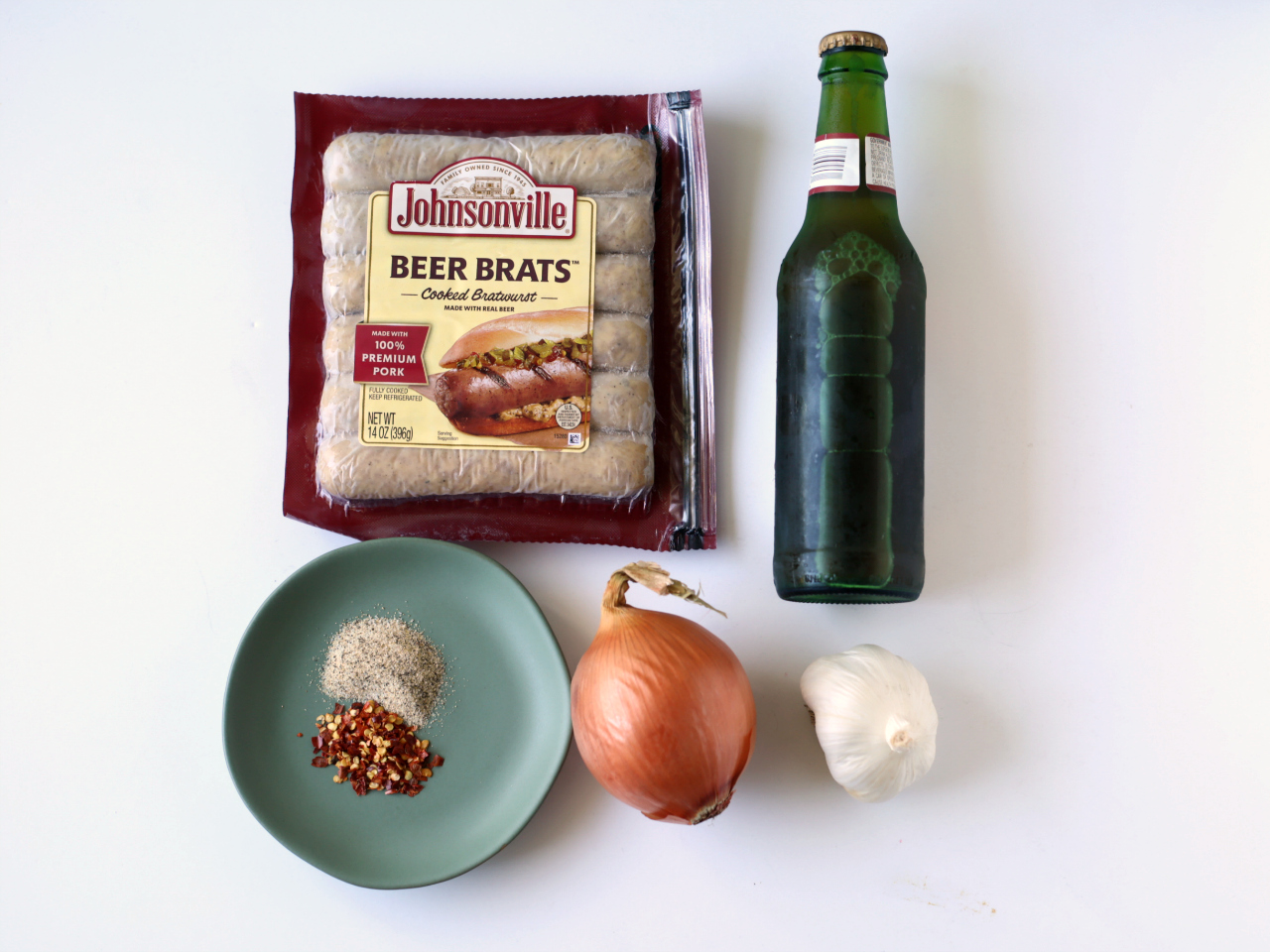 Johnsonville Beer Brats in package, seasonings on a blue plate, whole onion, whole garlic, a bottle of beer.