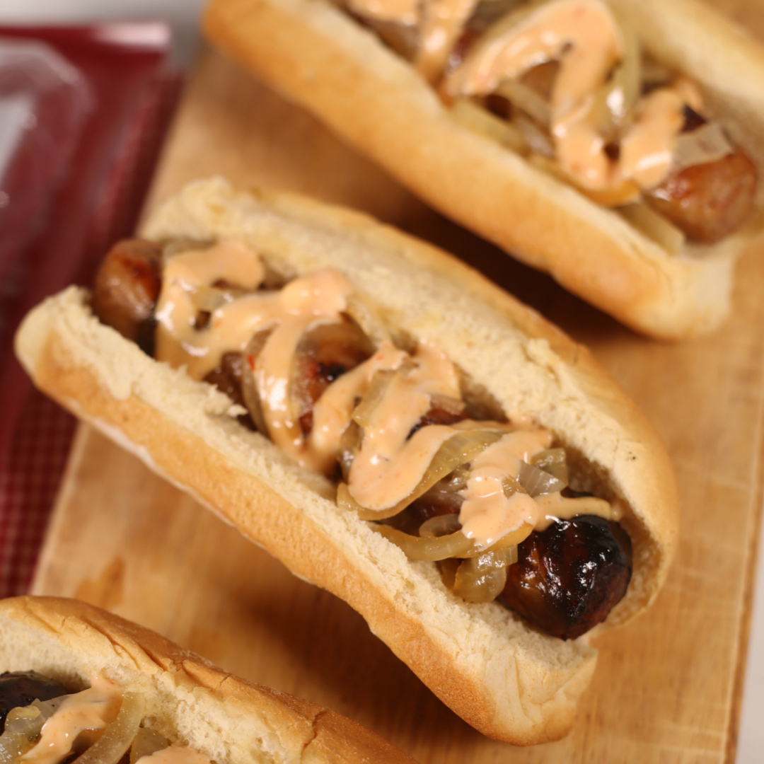 Grilled Beer Brats on a wooden plate.