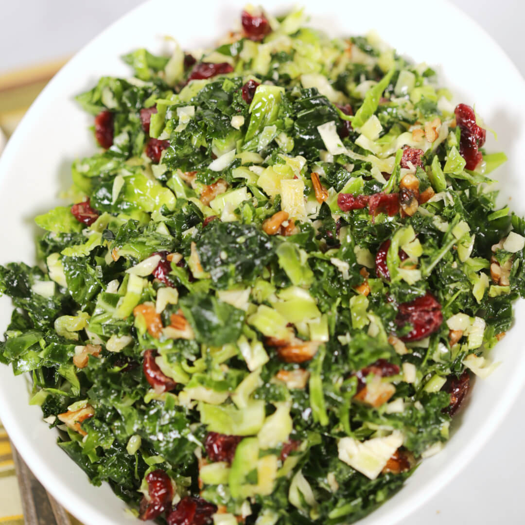 Kale Brussel Sprouts Salad in a white bowl with a yellow, green and red napkin.
