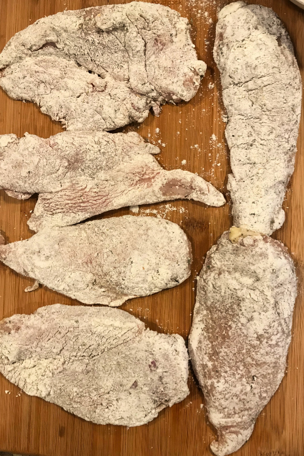 Raw chicken breast covered in flour