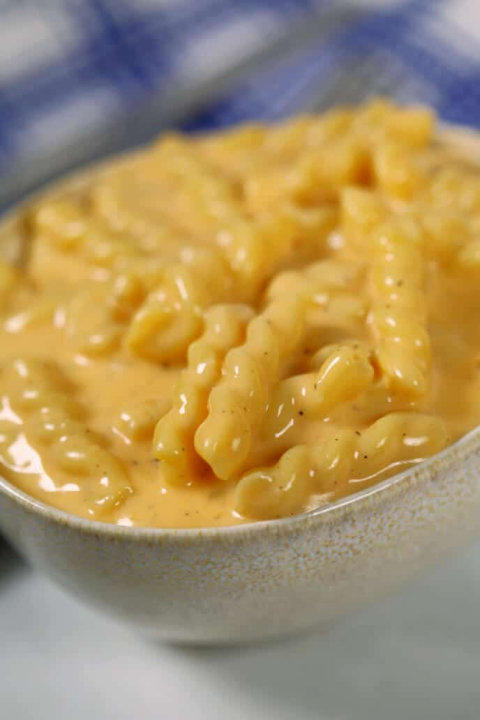 a close up bowl of instant pot macaroni and cheese with a blue plaid napkin