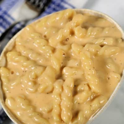 Macaroni and cheese in a small bowl with a blue plaid napkin and fork