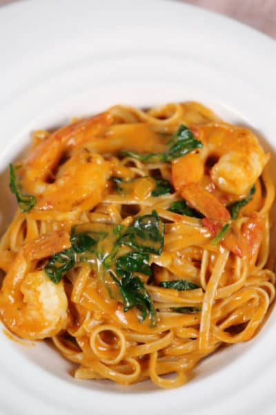 Shrimp Spinach Pasta in Pink Sauce in a white bowl on a pink placemat