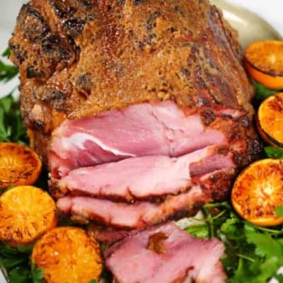 Honey baked ham recipe on a platter with greens and oranges