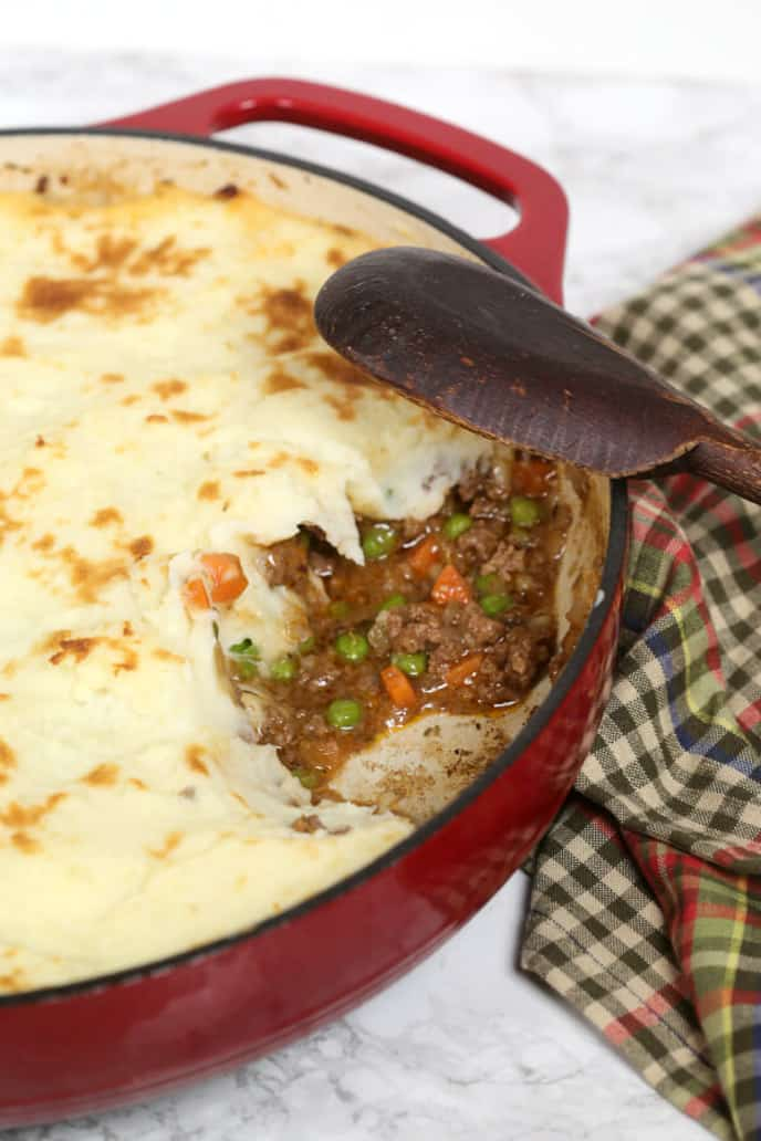 Shepherds Pie recipe in a red pan with a plaid napkin and wooden spoon