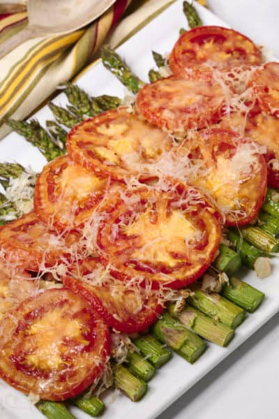 Easy asparagus recipe on a white platter with a striped napkin