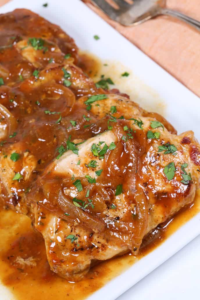 Pan Seared Drunken Pork Chops with Beer on Whitet Plate with chopped herbs